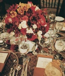 Gold plates on brown tablecloth with red flower centerpiece