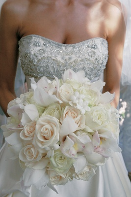 White bouquet of roses, orchids, and stephanotis with touches of pink