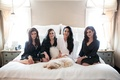 bride in white robe, bridesmaids in black robe on bed with dog