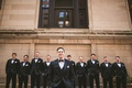 wedding photo groom in tuxedo bow tie white pocket square groomsmen in matching tuxedo suits