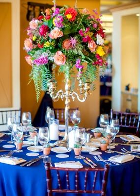 round navy tablescape vibrant florals tall arrangement silver candelabrum spanish flair wedding