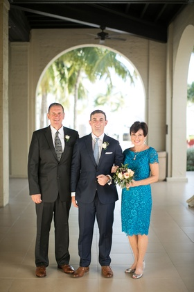 Mother of the groom in blue teal lace scallop dress with short sleeves below the knee hem bouquet