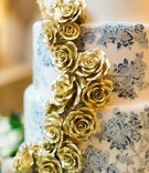 wedding cake with blue and white ombre flower design and gold sugar flowers down side