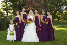 Bride with flower girl and bridesmaids in strapless purple gowns