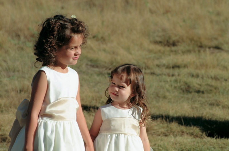 Young girls in white dresses with champagne sash