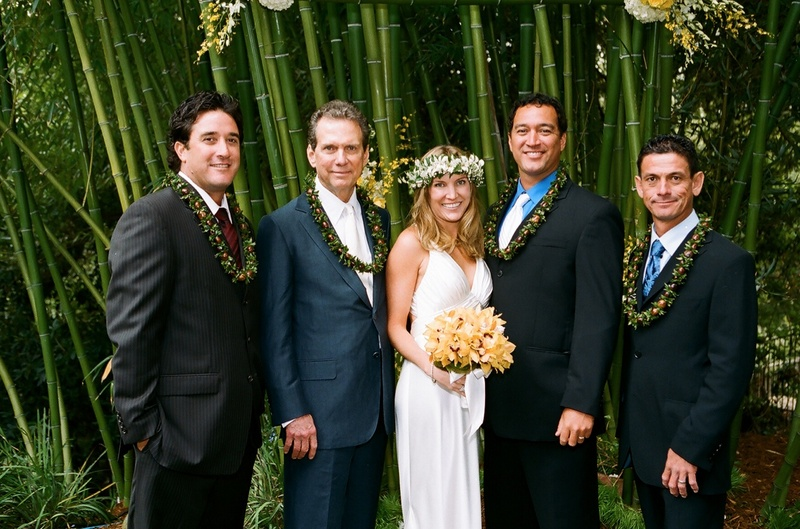 Bride with male guests wearing Hawaiian lei