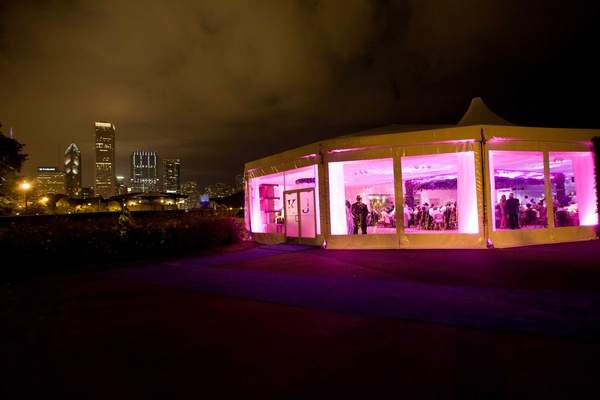 a white wedding tent with pink and purple lighting sitting in a garden outside of chicago illinois