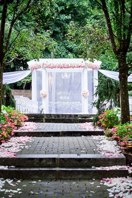 wedding ceremony bricks with white pink flower petals ceremony arbor pink flowers white drapes