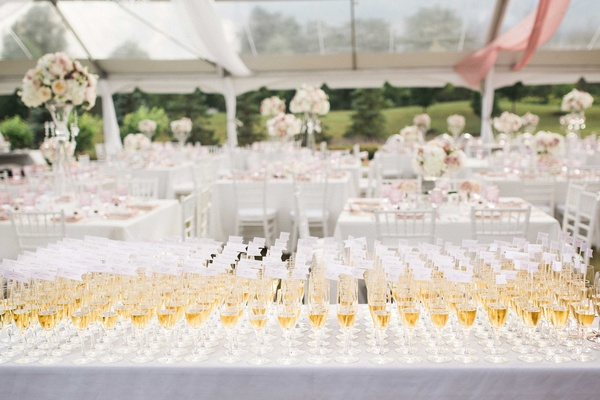 table full of glasses of champagne with flags in the flutes