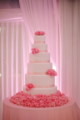 Six layer white cake with pink ribbons and fresh roses