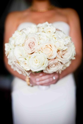 Bride holding blush and peach rose flowers
