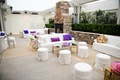 White tufted sofas and ottomans at wedding lounge area
