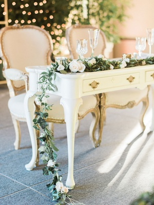 white antique desk sweetheart table throne chairs garland greenery white flowers