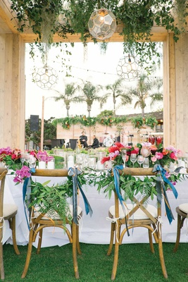 wedding reception bride groom chairs decorated with ribbon and greenery pink centerpieces tropical