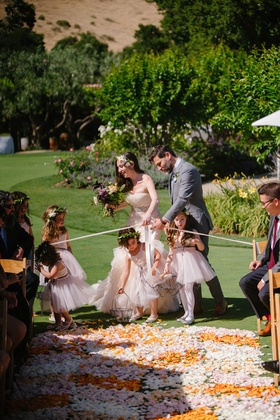 bride and groom help flower girls into aisle blocked with ribbon