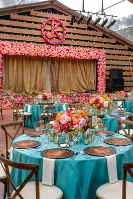 Wedding reception with a wood stage framed by pink and orange flowers, pink flower initials