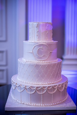 White wedding cake with a different piped pattern on each layer, initial of couple's surname