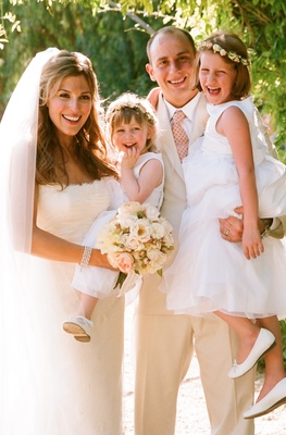 Bride and groom hold young flower girls