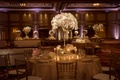 Wedding reception tables with flower and jewel centerpieces featuring orchids and roses