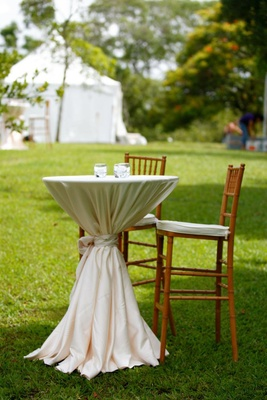 Outdoor wedding cocktail hour with table covered in white tablecloth is surrounded by wood chairs
