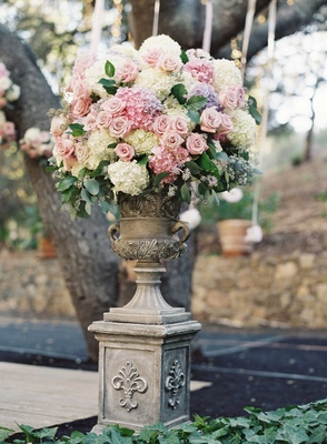 Stone urn wedding flower arrangement with rose and hydrangea flowers in purple, pale blue, and ivory