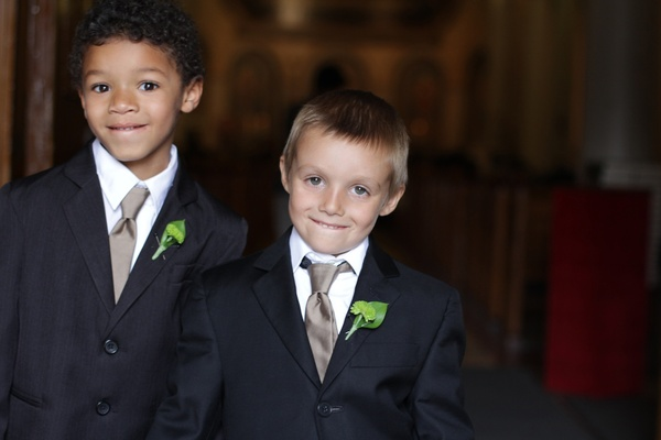 Ring bearer in suit with taupe tie and green boutonniere