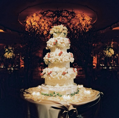 White wedding cake decorated with white and pink roses