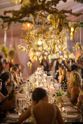 wedding reception with gold grapewood branches and individual white flowers hanging down