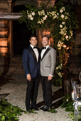 same-sex wedding gay couple, groom in navy tuxedo jacket & groom in grey tuxedo jacket under arch