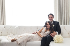 bride in eddy k couture, groom in calvin klein, bride leaning on groom's lap lying on couch