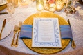Gold ornate charger plate and gold flatware fork knife with candles and light blue napkin menu card