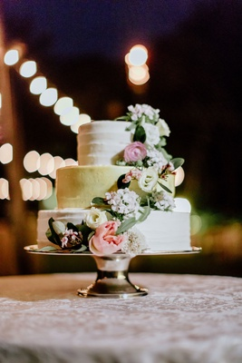 three layer white and gold wedding cake with freseh ivory pink flowers rose greenery cake stand