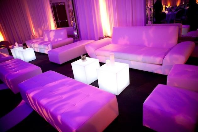 White wedding lounge chairs with fuchsia lighting