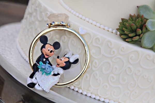 Mickey and Minnie Mouse sitting in large engagement ring