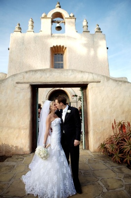 Bride and groom in front of adobe style church
