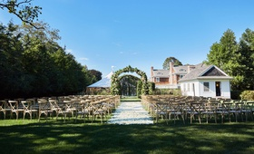 wedding ceremony on grass lawn wood vineyard x back chairs white flower petal aisle greenery arch