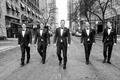 Black and white photo of groom and groomsmen in tuxedos and bow ties walking down chicago street
