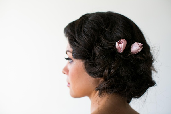 Bridesmaid with loose updo and pink rosebud