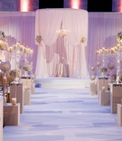 Wedding ceremony in draped section with ivory flower arrangements and crystal candelabra