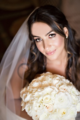 half-up hairstyle, light makeup on bride holding white bouquet of flowers