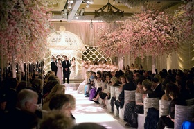 White ruched ceremony chairs and pink trees