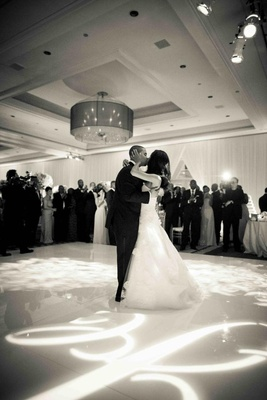 Black and white photo of bride and groom kissing on dance floor