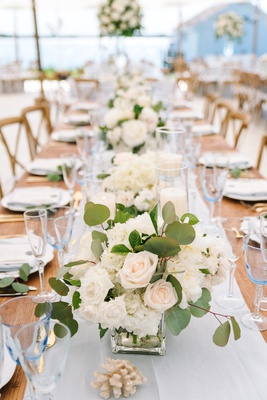 head table with small centerpieces down the middle with rose and eucalyptus leaves
