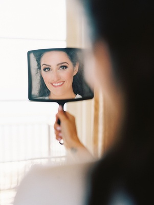 bride looks gazes at herself in a hand held mirror beauty makeup hair hairstyles