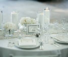 Wedding reception table with white tablecloth, stone runner, candles, and flowers