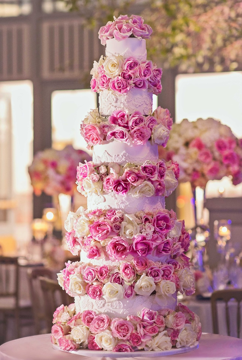 Tall white wedding cake with six layers fresh pink rose white rose flowers in between each tier