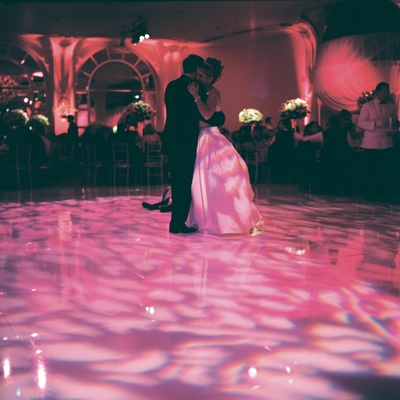 Bride and groom dancing in pink and purple light