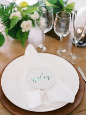 Wedding reception wood table low centerpiece flowers white plate white napkin white place card