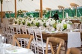 Tent wedding reception with long king's tables green goblets glassware wood chairs white runner