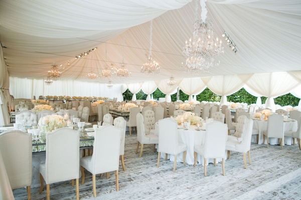 Tent wedding reception chandeliers whitewash wood flooring beige dining chairs glass crystal tables